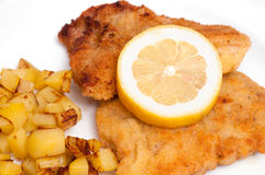 Veal cutlet with coating and lemon slice and chips Royalty Free Stock Image