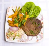 Veal cutlet with leaves of salad and fried potatoe stock image
