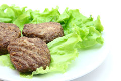 Veal cutlet with lettuce on white background. Veal cutlet steamed with lettuce on white background Royalty Free Stock Images