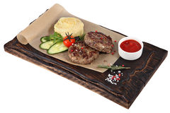 Veal cutlets with mashed potatoes on serving plate dark red. Royalty Free Stock Photography
