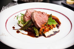 Veal fillet with vegetable ratatouille. Parsnip puree, asparagus and bone marrow sauce stock image