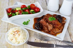 Veal meat cooked with smoked prunes on a white plate with fresh vegetable salad and boiled rice. Healthy eating concept. Royalty Free Stock Photography
