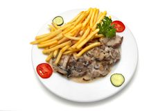 Veal medallion with mushroom white sauce and french fries. Decorated with parsley, slices of tomato and cucumber Royalty Free Stock Photography