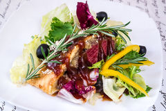 Veal with mushrooms in puff pastry and vegetables. On a white plate royalty free stock photography