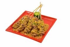 Veal satay. Black plate with chicken satay on white royalty free stock photos