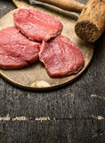 Veal schnitzel preparation on rustic wooden background with old meat hammer Royalty Free Stock Photography