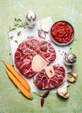 Veal shank slices meat and ingredients for Osso Buco cooking, composing on rustic wooden background Royalty Free Stock Photo