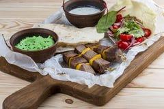Veal shashlik with green hummus and Dzadziki sauce with horseradish stock photos
