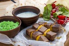 Veal shashlik with green hummus and Dzadziki sauce with horseradish stock photography