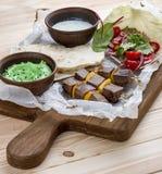 Veal shashlik with green hummus and Dzadziki sauce with horseradish stock image