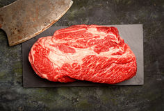 Veal steak marbled basalt, a knife for meat on a dark background. Veal steak marbled basalt, a knife for meat royalty free stock image