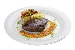 Veal steak with salsa on a white plate stock image