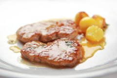 Veal steak in sauce. Main course veal with a sauce and baked potato Stock Image