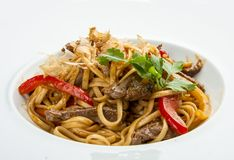 Veal with udon noodles on a white plate royalty free stock photos