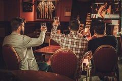 Vecchi amici allegri che guardano gli sport e che bevono la birra alla spina in pub fotografia stock