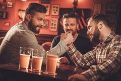 Vecchi amici allegri che hanno sfida di braccio di ferro in un pub fotografie stock