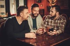Vecchi amici allegri divertendosi e bevendo la birra alla spina in pub fotografia stock