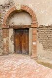 Vecchi arco e porta della costruzione di missione Fotografia Stock