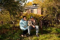 vecchi arrugginiti della base del giardino d'autunno delle coppie si siedono fotografia stock