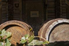Vecchi barilotti di vino sul fondo di legno della porta con il globo arrugginito del barilotto all'aperto fotografia stock libera da diritti