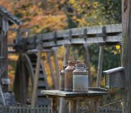 Vecchi bidoni di latte su una tavola, mulino a acqua nei precedenti, autunno Fotografia Stock