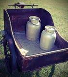 Vecchi bidoni di latte trasportati in vecchio vagone con la bicicletta arrugginita Immagini Stock