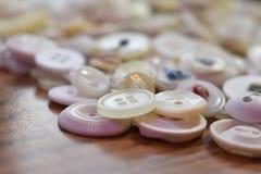 Vecchi bottoni di cucito bianchi su legno Fotografia Stock