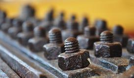 Vecchi bulloni arrugginiti d'annata con i dadi su grande di piastra metallica Immagini Stock Libere da Diritti