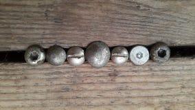 Vecchi bulloni del metallo sul legno Fotografia Stock