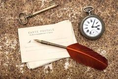 Vecchi cartoline, orologio, chiave e penna della piuma Immagine Stock