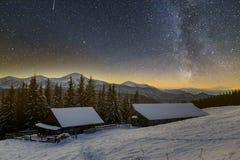Vecchi casa, capanna e granaio di legno, mucchio di legna da ardere in neve profonda sulla valle della montagna, foresta attillat fotografia stock libera da diritti