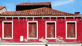 Vecchi casa e tetto della finestra con la parete rossa fotografia stock