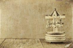 Vecchi cavalli bianchi d'annata del carosello sulla tavola di legno foto in bianco e nero di vecchio stile Immagine Stock