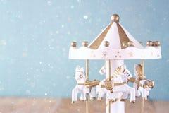 Vecchi cavalli bianchi d'annata del carosello sulla tavola di legno retro immagine filtrata con la sovrapposizione di scintillio Fotografie Stock Libere da Diritti