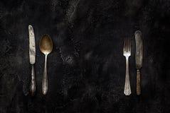 Vecchi coltello, cucchiaio e forchetta della fattoria sulla vista superiore concreta Fotografie Stock