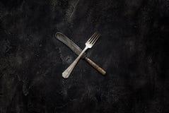 Vecchi coltello della fattoria e forcella X sulla vista superiore concreta Fotografia Stock