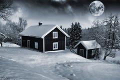Vecchi cottage e luna piena nel paesaggio di inverno Immagine Stock