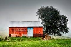 Vecchi cottage ed albero rossi in una zona rurale nebbiosa Fotografie Stock