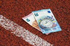 Vecchi cronometro e soldi di sport sulla gomma corrente della pista fotografia stock