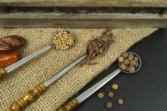 3 vecchi cucchiai del metallo con le spezie sul fondo della tela da imballaggio Fotografia Stock