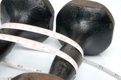 Vecchi dumbbells del ferro e misura di nastro Immagini Stock