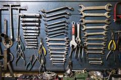 Vecchi e strumenti trascurati sporchi impilati in una vecchia officina con l' Fotografia Stock