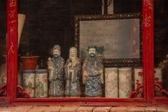 Vecchi figure e vasi cinesi antichi su esposizione in una struttura della finestra rossa a Pechino, Cina fotografia stock libera da diritti
