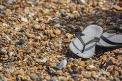 Vecchi flip-flop sulla spiaggia rocciosa immagini stock
