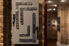Vecchi fori della porta e maniglie - entrata di legno sui mura di mattoni - maniglie fatte di metallo fotografia stock