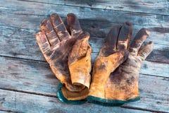 Vecchi guanti del lavoro sporco di vista superiore su una tavola di legno macchiata con grasso ed olio Le professioni del duro la immagine stock libera da diritti