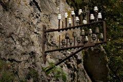 Vecchi isolanti elettrici su una parete della roccia Immagini Stock
