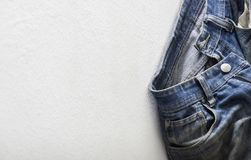 Vecchi jeans blu che appendono su una parete immagini stock