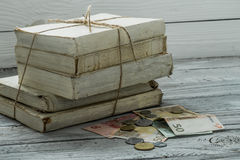 Vecchi libri bianchi con soldi e monete su fondo di legno Fotografia Stock