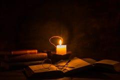 Vecchi libri che sono letti dalla luce della candela Fotografie Stock